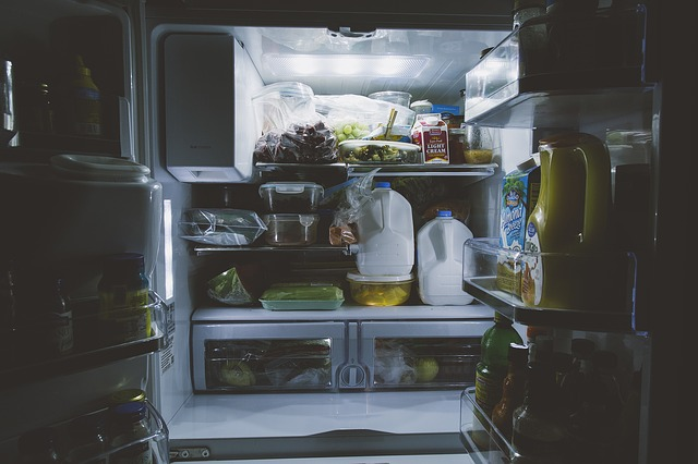 small home refrigerator filled to the brim with food items