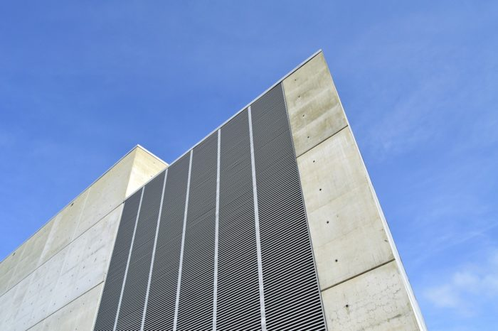 A picture of a gray building with the blue sky behind it.