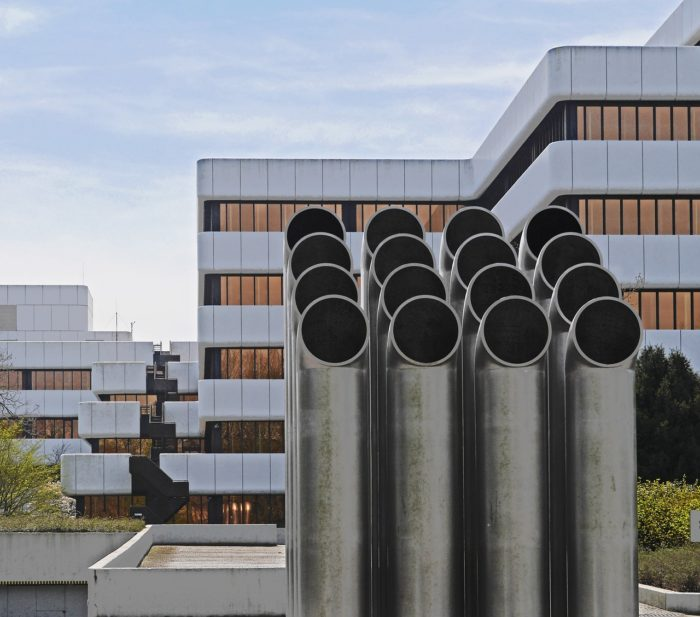 Numerous gray large vents in front of a large white building with rose gold tinted windows