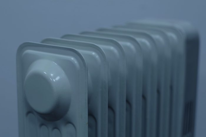 A close up of a small white heater in a white background