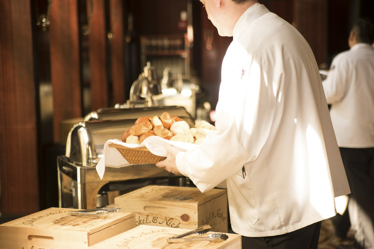 Waiter grabbing bread from a kitchen