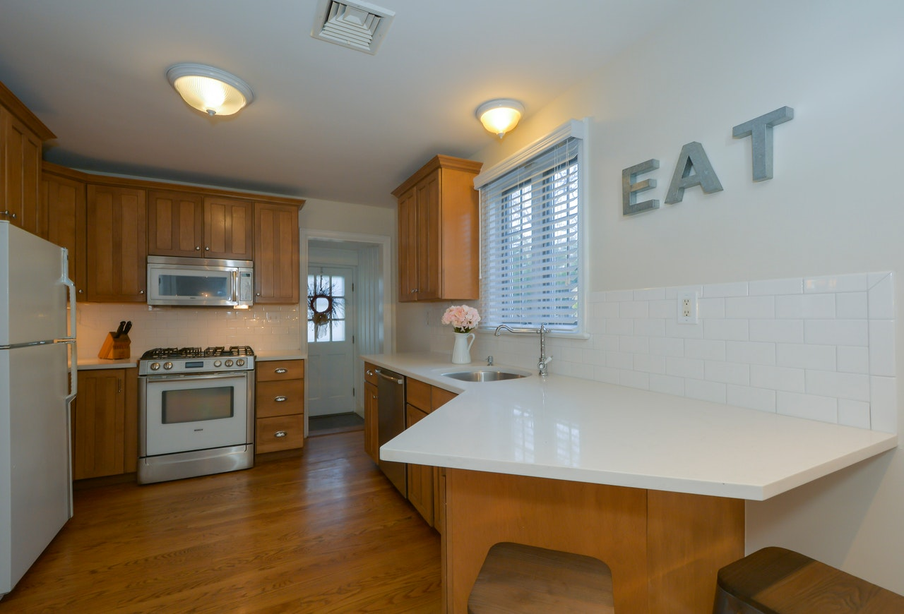 A kitchen with a sign that says eat on the wall