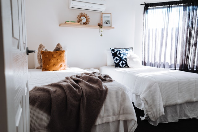 two beds with white sheets and accents